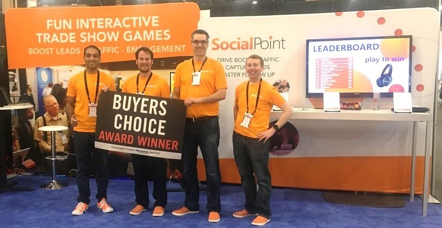 SocialPoint team at EXHIBITORLIVE 2018 celebrates winning Buyers Choice Award next to trade show trivia game leaderboard